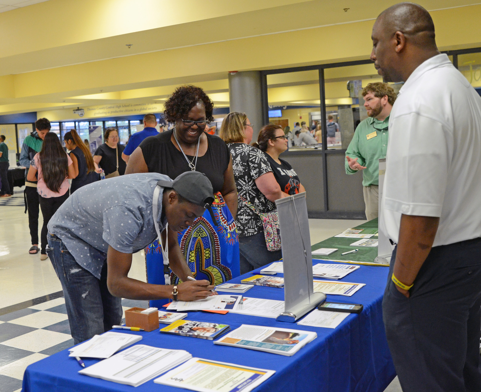 TCCHS English teacher Renae Moore and senior James Jones interact with a college representative to obtain more information about Albany State University.