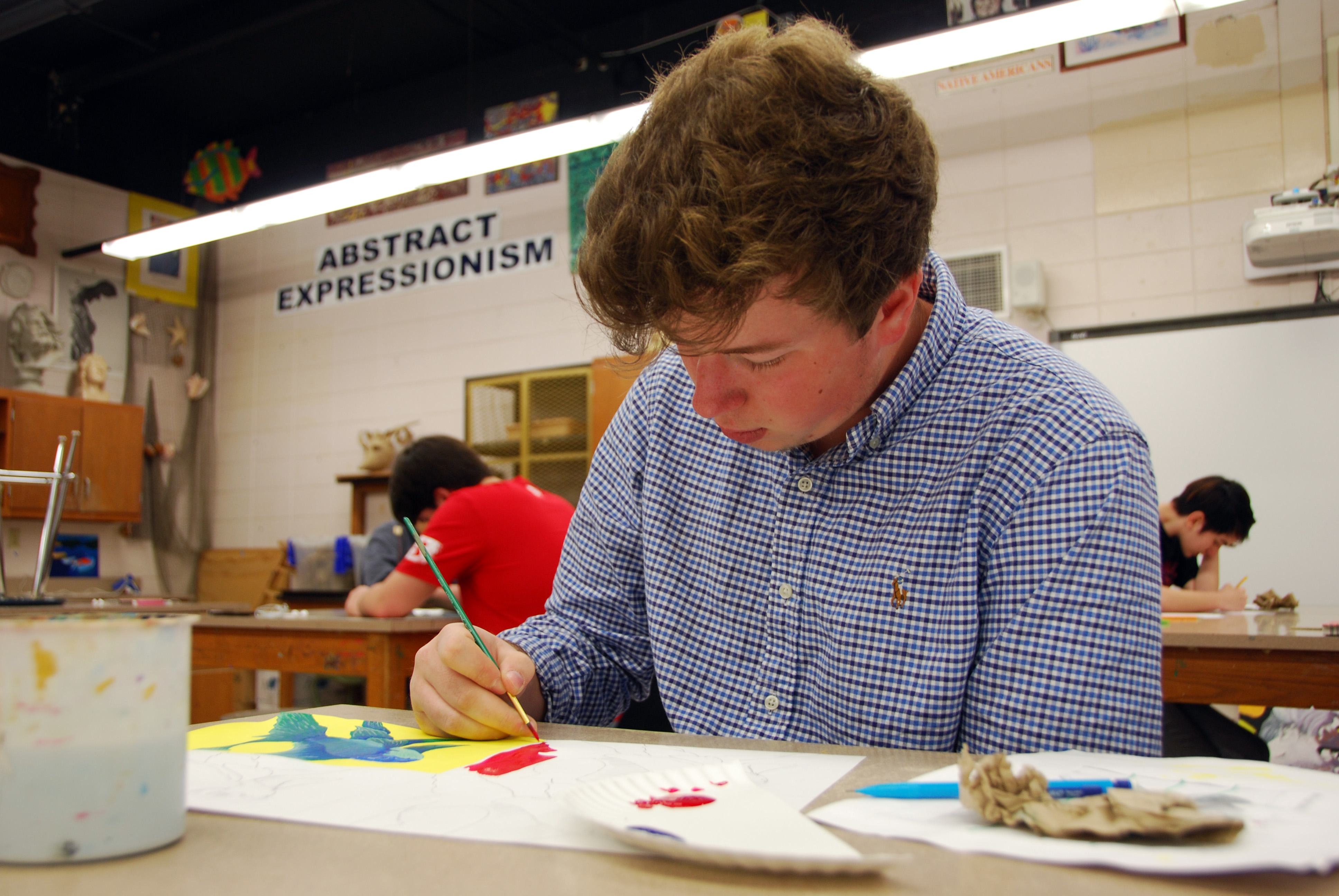 "TCCHS Senior Chris Harry paints ""Warhol-style Goldfish"" for one of his twelve fish-themed artworks in AP Studio Art."