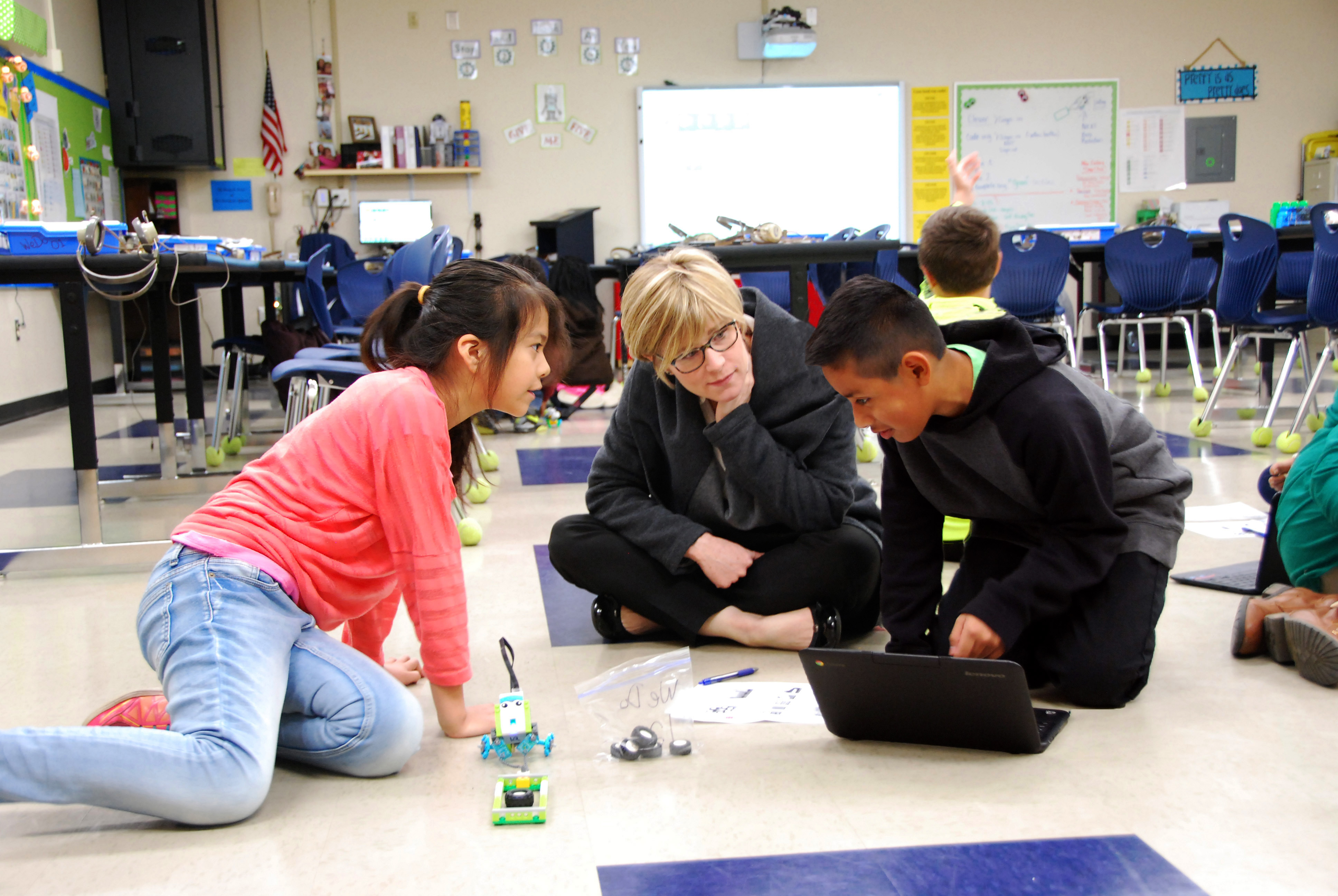 Dr. Caitlin Dooley (center), Georgia Department of Education Deputy Superintendent of Teaching and Learning, observes fourth graders Haley Gonzalez, from left, and Enrique Lopez as they program robots in the coding classroom at Cross Creek Elementary.