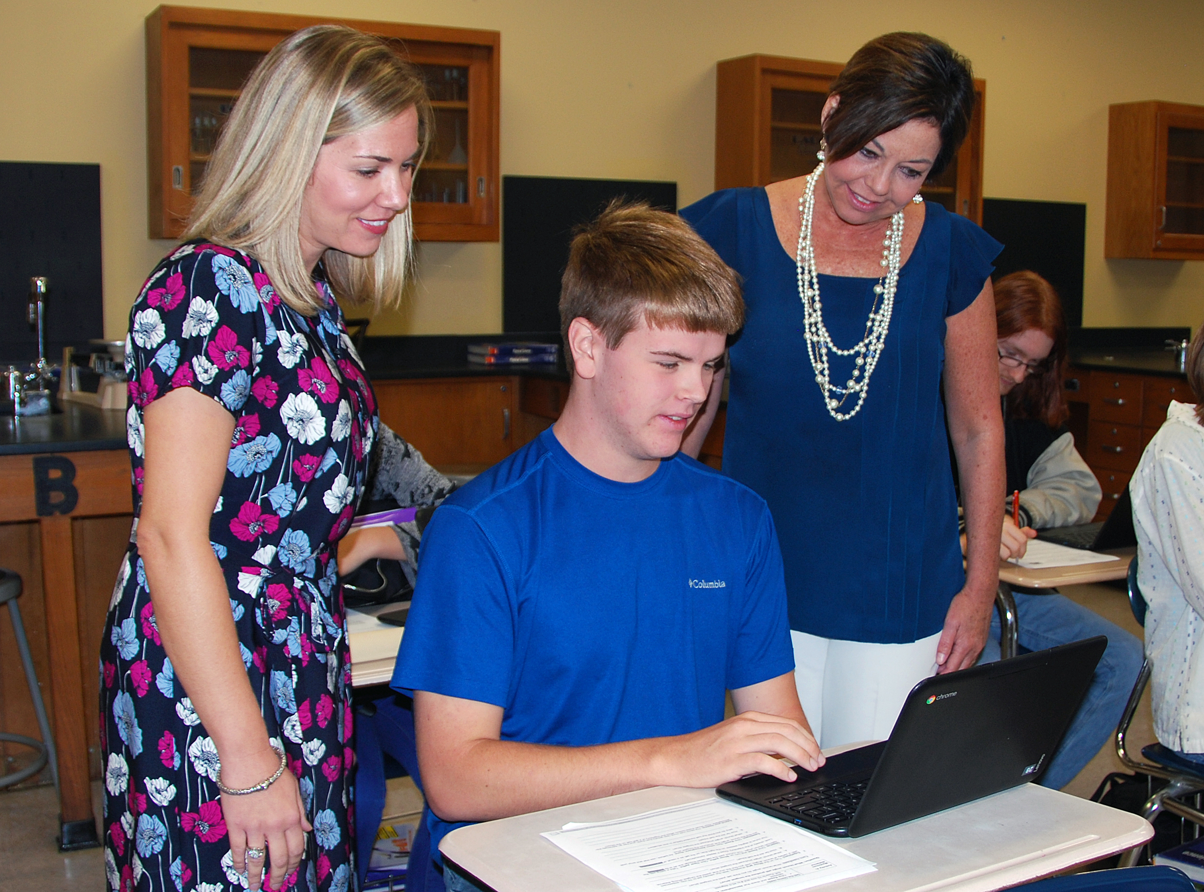 Instructional Technology Specialist Lindsay Thompson and TCCHS Principal Trista Jones observe Jackson Groom working on a Chromebook in Ryan Strickland's Physics classroom.