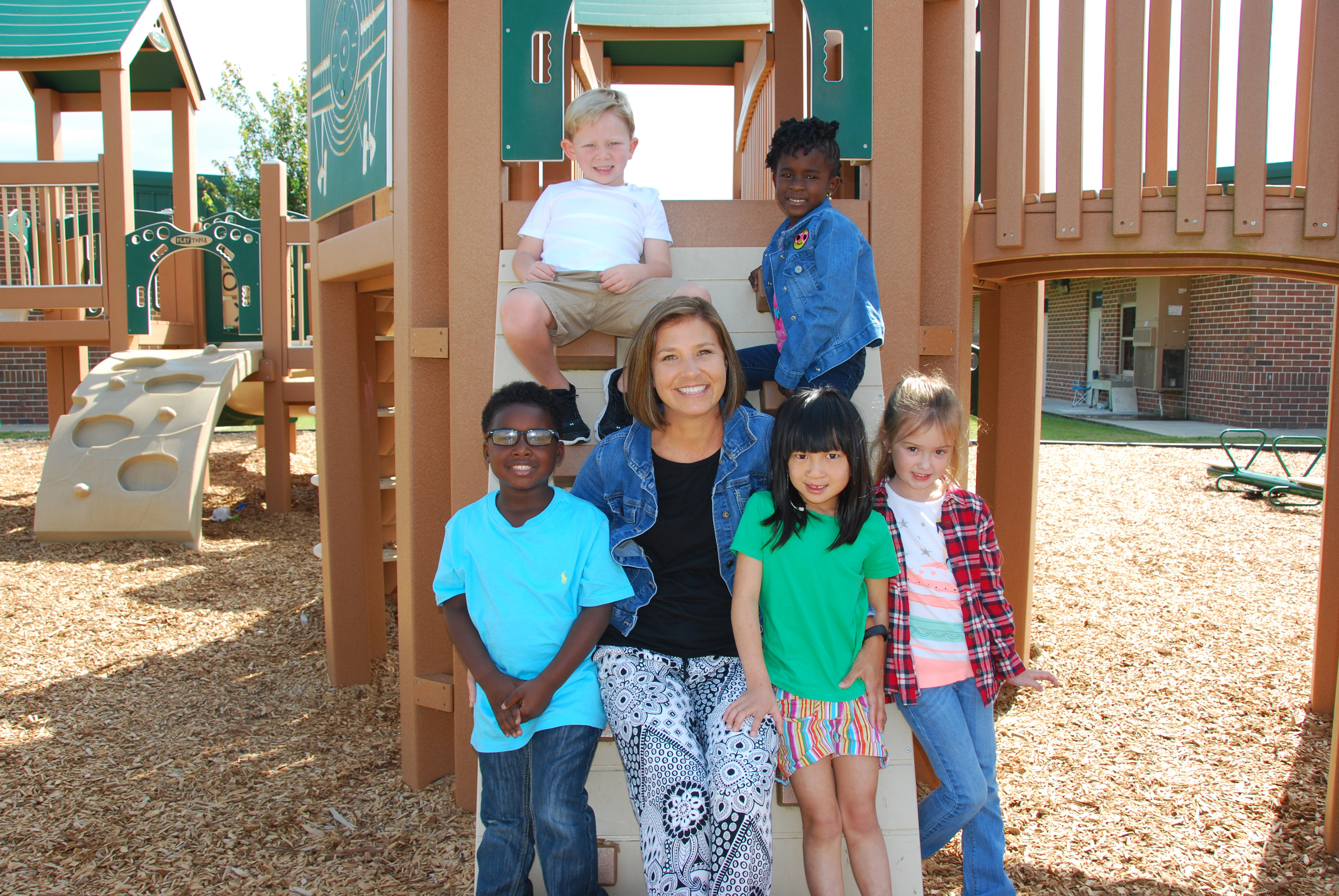 On the playground is Dee Gaines (center) surrounded by kindergarten students Xalen James, from left, Sam Stewart, Destiny Hobbs, Rosie Cooper, and Blake Knisely.