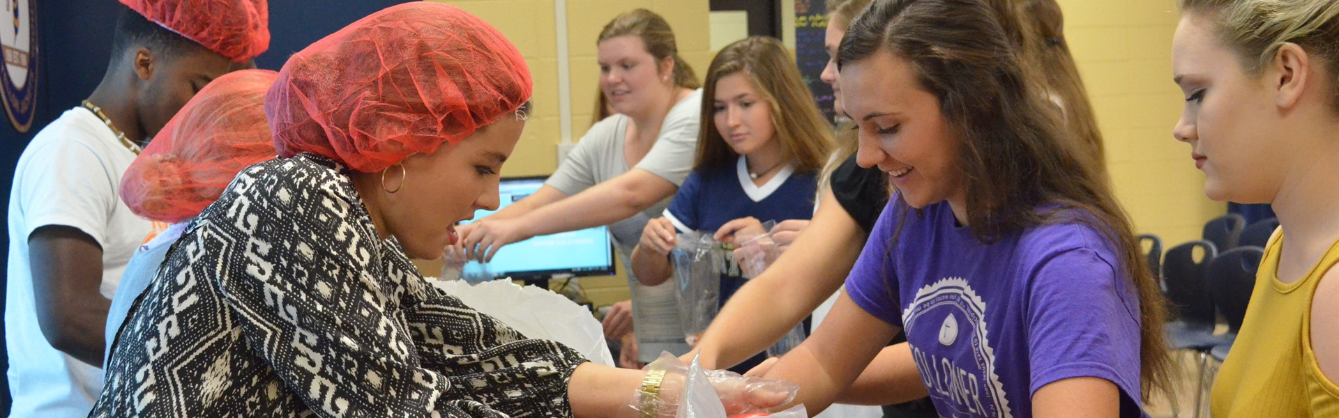 TCCHS students prepare food bags through the Chick-fil-a Leader Academy.