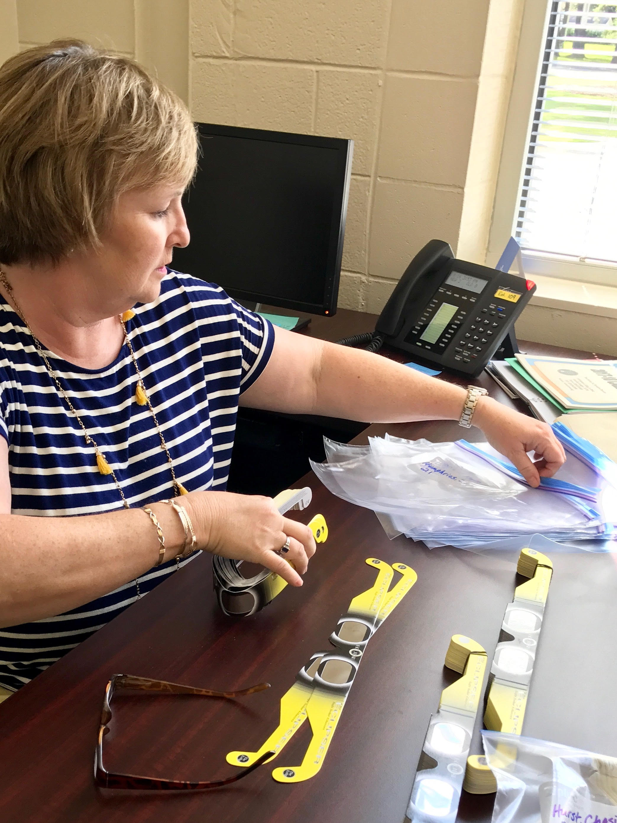 Robin Shaver, Elementary Curriculum Coordinator working with solar eclipse glasses for schools